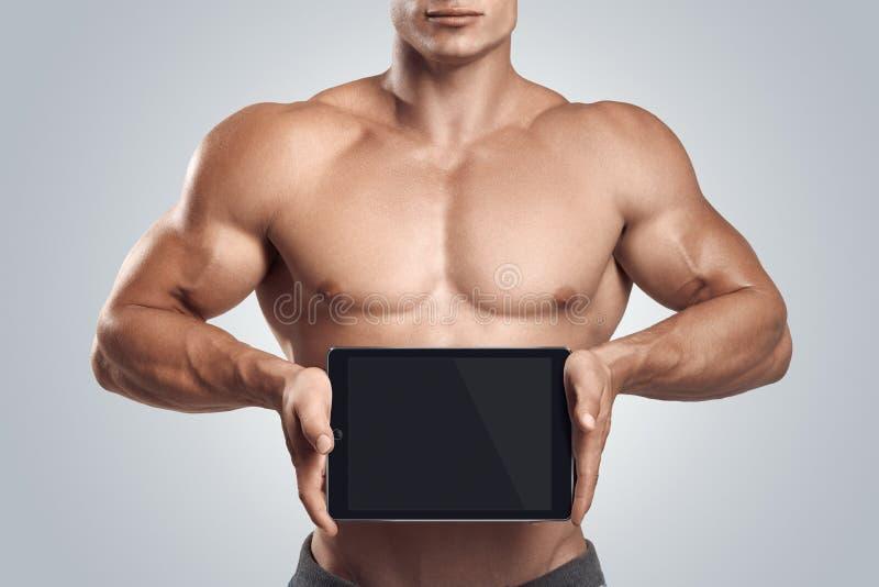 水平地拿着有空白的scre的健身男性数字式片剂 免版税库存图片