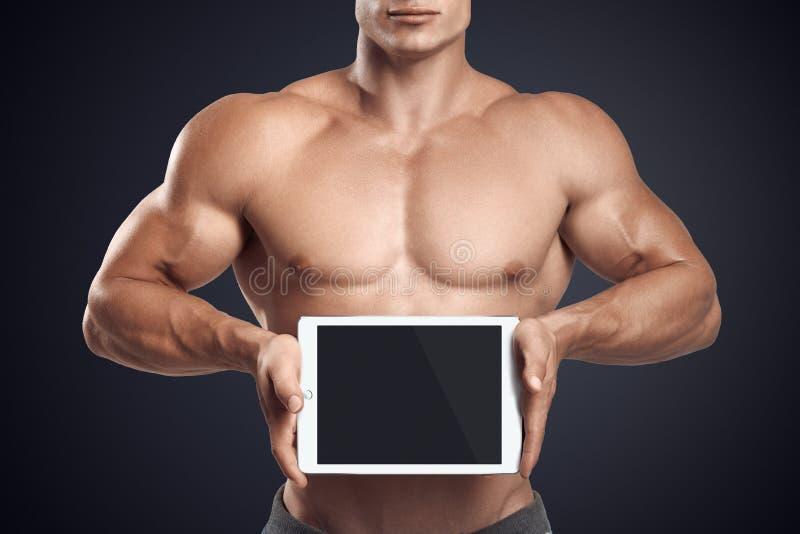 水平地拿着有空白的scre的健身男性数字式片剂 库存照片