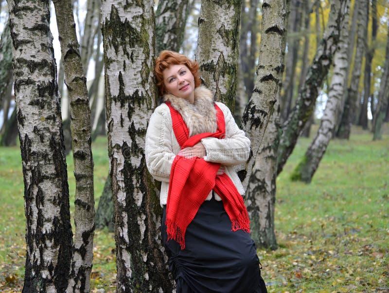 平均岁月的妇女倾斜了反对在木头的桦树 免版税库存图片
