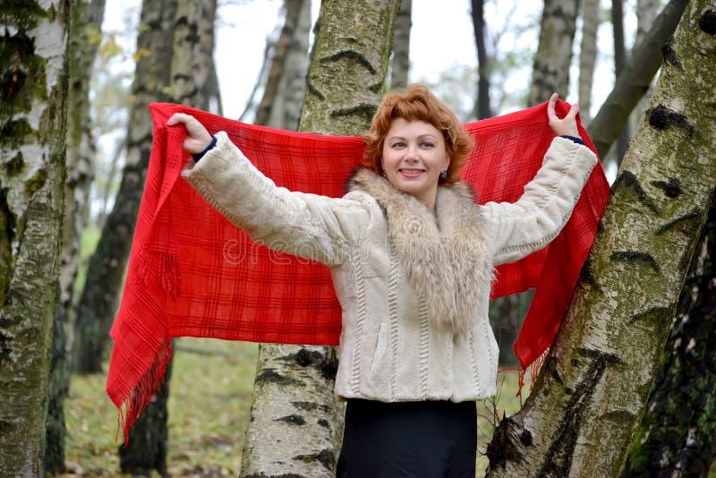 平均岁月的快乐的妇女在被举的手上拿着一个红色女用披肩 库存照片