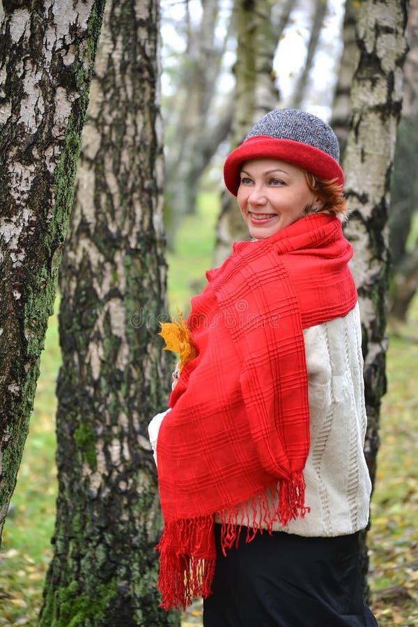 平均岁月的快乐的妇女的画象在红色女用披肩和帽子的 库存照片