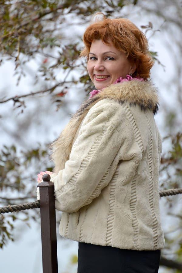 平均岁月的愉快的妇女的画象在一件轻的短的皮大衣的 免版税库存图片