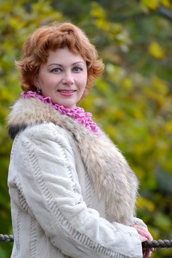 平均岁月的愉快的妇女的画象以秋天树为背景的 关闭 库存图片