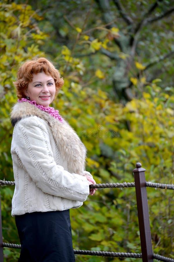 平均岁月的愉快的妇女的画象以秋天树为背景的 库存照片