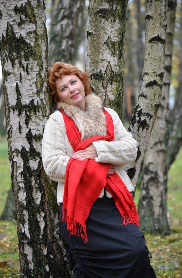 平均岁月的沉思妇女倾斜了反对桦树  免版税库存图片