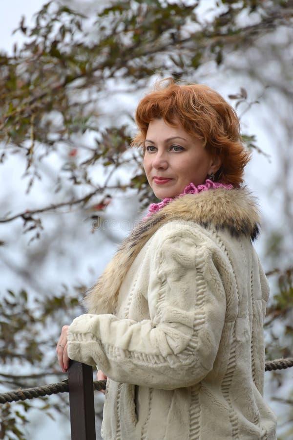 平均岁月的骄傲的妇女的画象在一件轻的短的皮大衣的 免版税库存照片