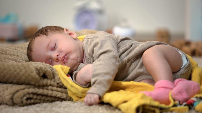 平安地睡觉可爱的新生儿的女孩,自然衣物和卧具 免版税图库摄影