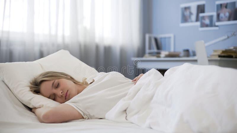 平安地睡觉在坏的美丽的青少年的女孩,放松在早晨,休息时间 免版税库存图片