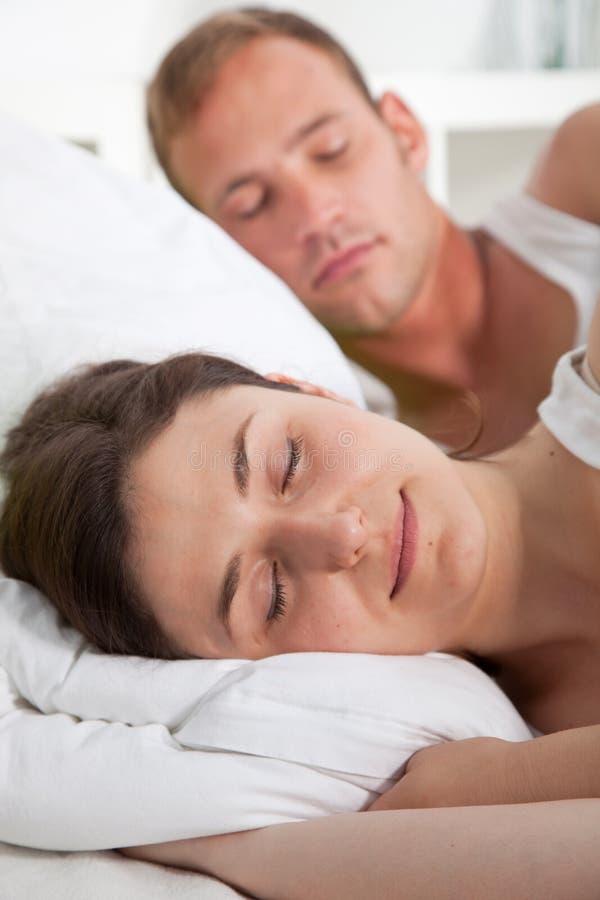 平安地睡觉在床上的可爱的少妇 免版税图库摄影