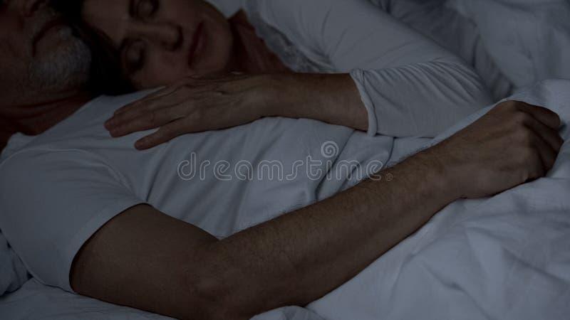 平安地睡觉在床,妻子上的年迈的夫妇说谎在丈夫胸口,亲热 图库摄影