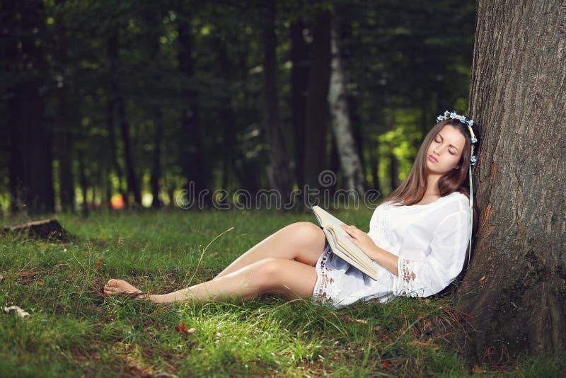 平安地睡觉在森林里的美丽的妇女 免版税库存照片