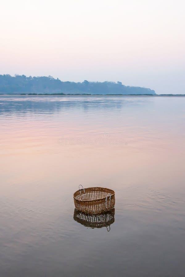 平安平静由河,一个竹篮子在湄公河浸洗在冬天早晨,静物画在农村老挝 库存图片