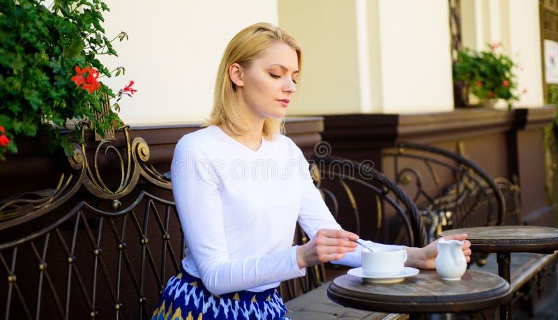 平安的咖啡休息 妇女典雅的镇静面孔有饮料咖啡馆大阳台户外 女孩每天早晨饮料咖啡在同样 库存照片