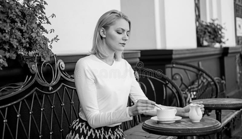平安的咖啡休息 妇女典雅的镇静面孔有饮料咖啡馆大阳台户外 女孩每天早晨饮料咖啡在同样 免版税库存图片
