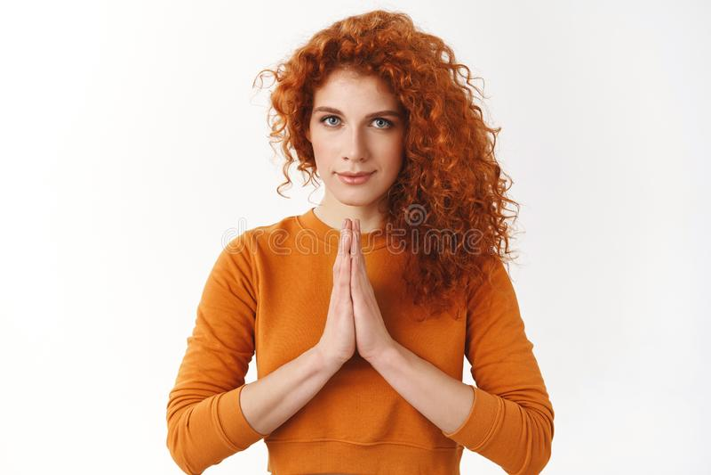 平安的悦目逗人喜爱的红头发人女性瑜伽辅导员,举行手一起祈祷标志,说namaste结束 免版税图库摄影