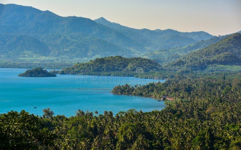 平安的海滩和蓝色海洋有山背景 图库摄影