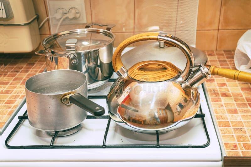平底深锅、一个煎锅和一个水壶在煤气炉 免版税库存图片
