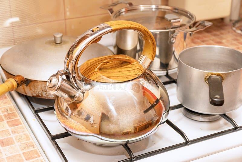 平底深锅、一个煎锅和一个水壶在煤气炉 库存照片