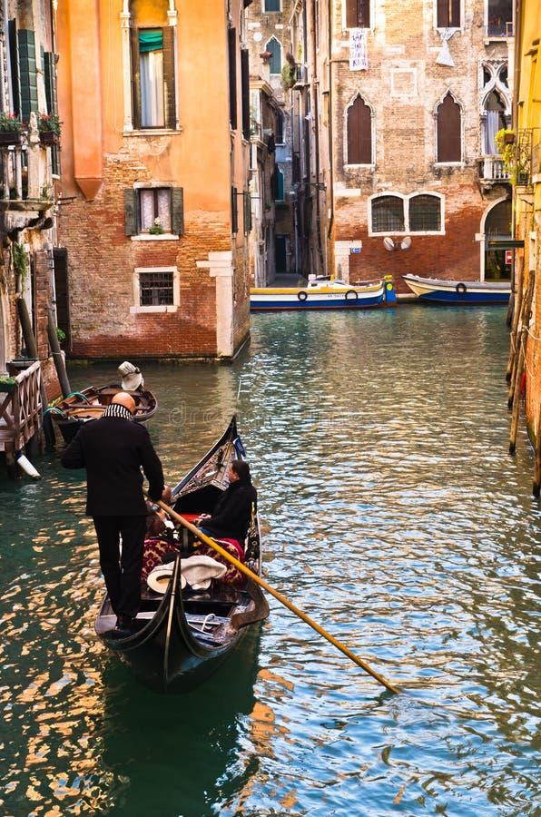 平底船的船夫驾驶长平底船在狭窄的渠道在威尼斯 图库摄影