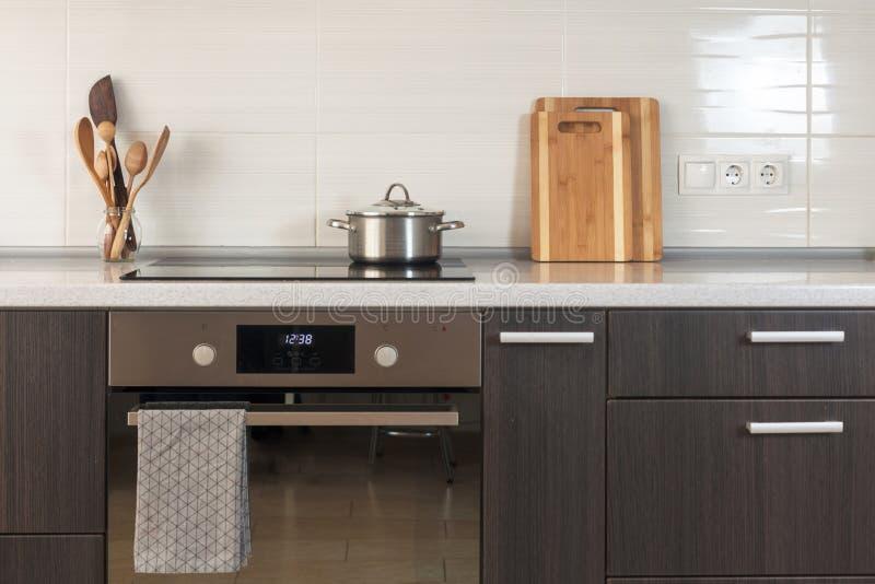 平底锅在一个陶瓷火炉 有烤箱、切板和厨房器物的其他元素的轻的厨房 库存图片