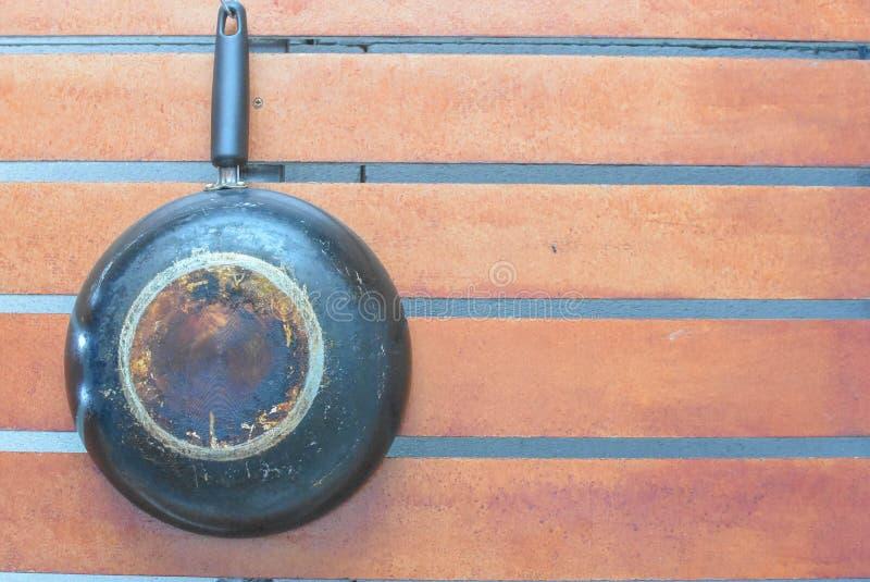 平底锅在木背景垂悬了 免版税库存照片