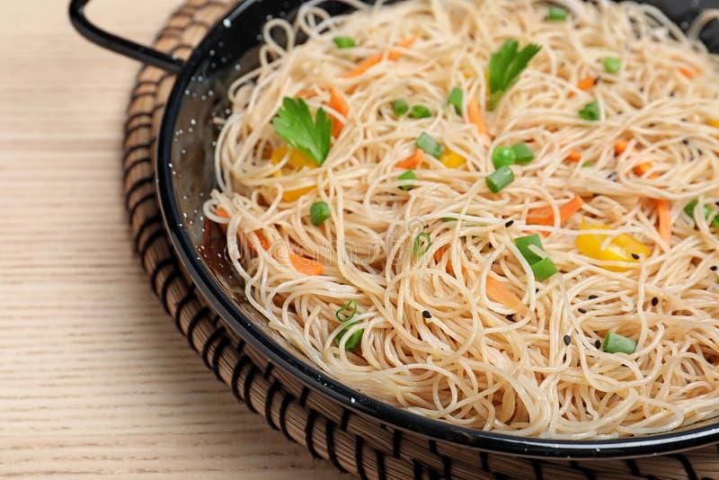 平底锅用可口亚洲面条和菜在木背景 免版税库存图片