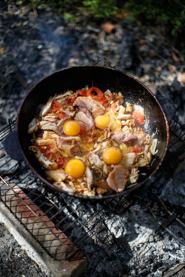 平底锅荷包蛋用烟肉和蕃茄由火 库存照片
