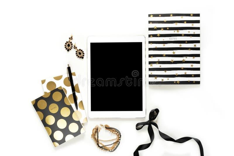 平的与电话、咖啡,时髦的黑金笔记本、化妆用品和首饰的位置时尚女性家庭办公室工作区 免版税库存图片