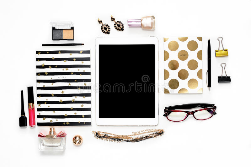 平的与电话、咖啡,时髦的黑金笔记本、化妆用品和首饰的位置时尚女性家庭办公室工作区 免版税库存照片