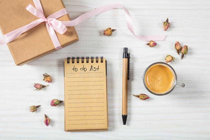 平的位置和礼物盒、邀请和清单在一个白色木桌面,背景,空白顶视图  图库摄影