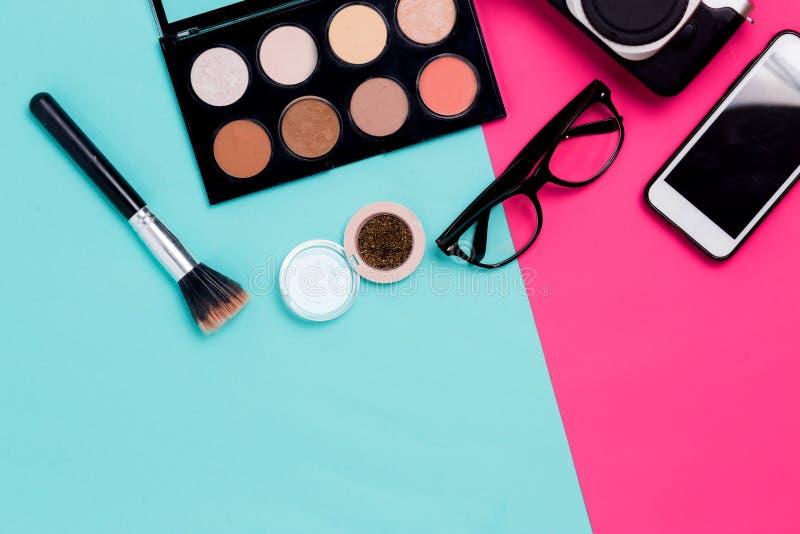 平的位置妇女的在五颜六色的蓝色和桃红色背景的旅行辅助部件与化妆用品、智能手机、玻璃和照相机 特写镜头, 免版税库存照片