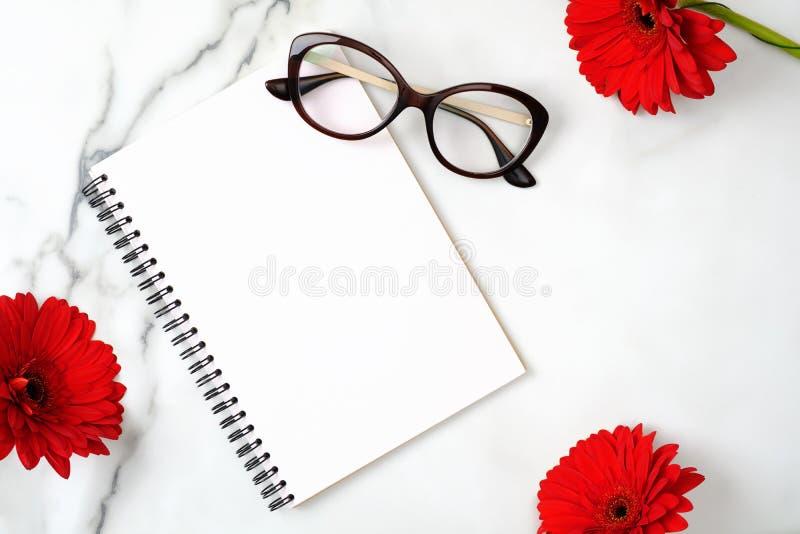 平的位置妇女的家庭办公室书桌 与纸笔记薄、女性玻璃、咖啡杯和雏菊花的工作区在大理石 免版税库存照片