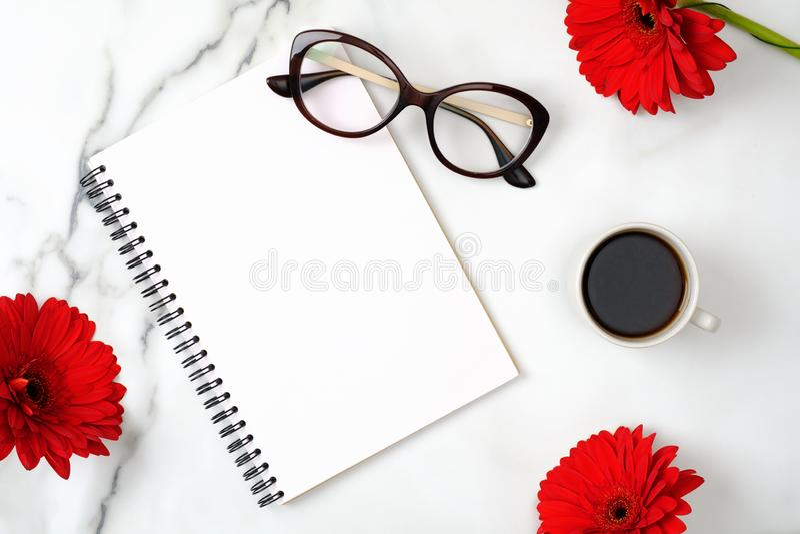 平的位置妇女的家庭办公室书桌 与纸笔记薄、女性玻璃、咖啡杯和雏菊花的工作区在大理石 图库摄影
