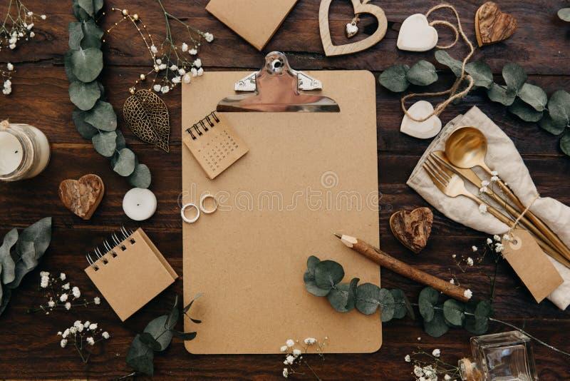 平的位置婚礼计划 制作有土气装饰的剪贴板在木背景 免版税图库摄影