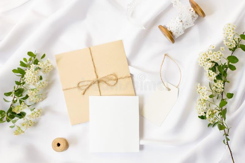 平的位置工作区,大模型 婚礼邀请卡片、工艺信封、白花、绿色叶子和鞋带在白色 免版税库存图片