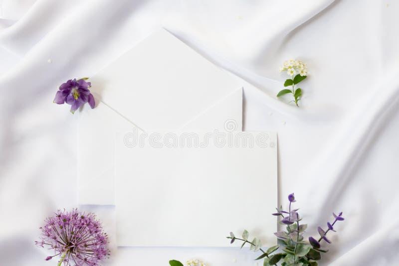 平的位置工作区,大模型 婚礼邀请卡片、工艺信封、紫色花、绿色叶子和鞋带在白色 库存照片