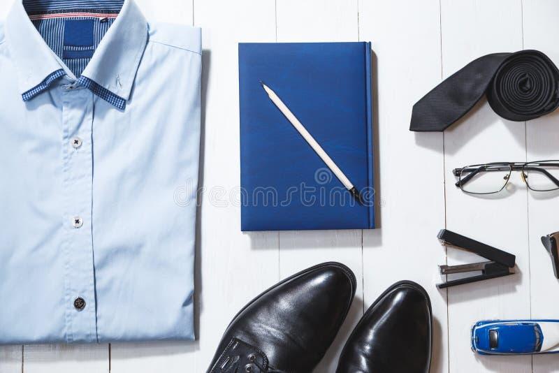 平的位置时尚套商人辅助部件,在白色木背景的顶视图 免版税库存图片