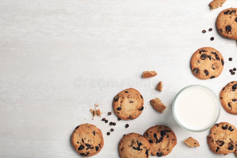 平的位置构成用巧克力曲奇饼和杯在轻的背景的牛奶 免版税库存照片