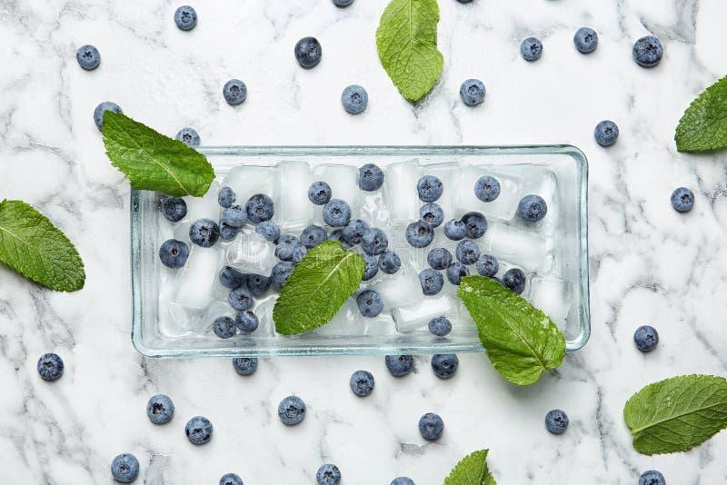 平的位置构成用水多的蓝莓、绿色叶子和冰 免版税图库摄影