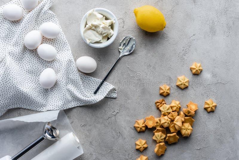 平的位置用被安排的柠檬、酸性稀奶油、未加工的鸡鸡蛋和曲奇饼饼的 免版税库存照片