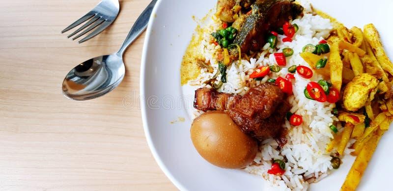 平的位置米混合了黄色咖喱鸡蛋、斑斑猪肉、红色和绿色辣椒和鱼在白色板材 库存照片