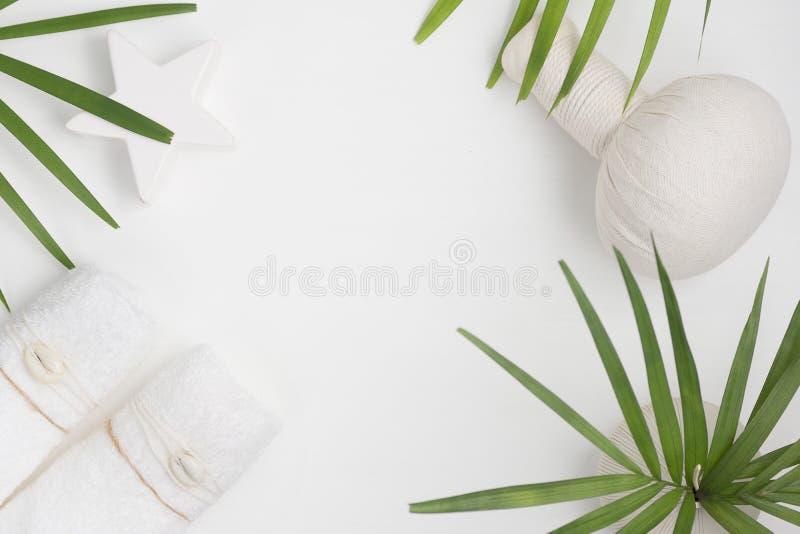 平的位置顶视图温泉背景:泰国按摩袋子、毛巾和棕榈叶在白色背景 健康生活方式 免版税库存图片