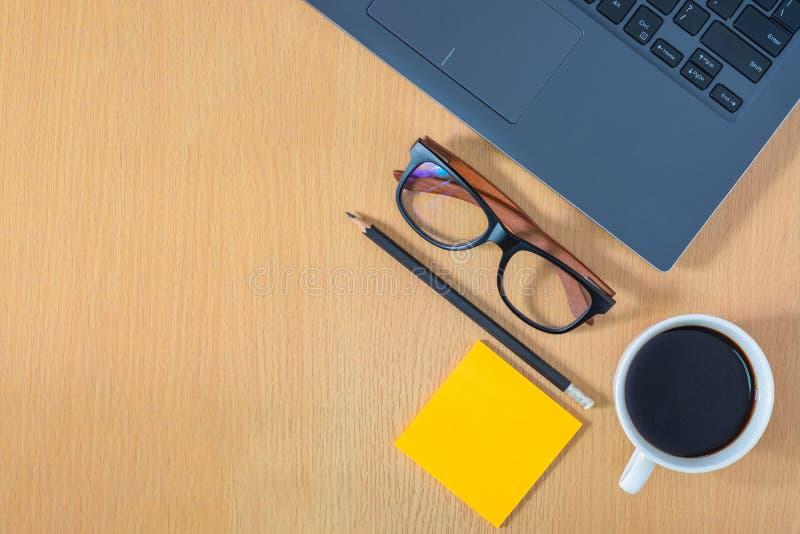 平的位置,顶视图工作区在办公室 使用膝上型计算机,玻璃,铅笔,加奶咖啡杯子,在木表上的办公用品 免版税库存图片