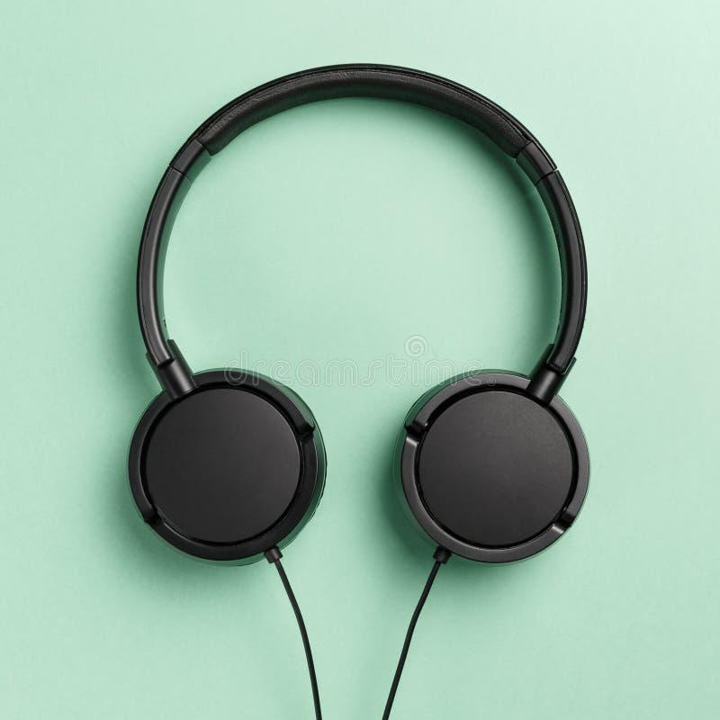 ?? : 平的位置:在薄荷的背景的耳机 免版税库存照片