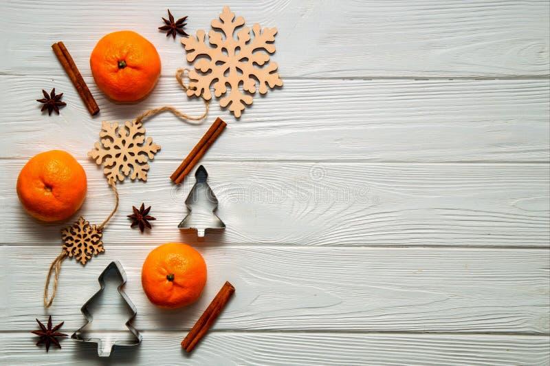 平的位置 白色土气桌用蜜桔,肉桂条,茴香星,酥皮点心的圣诞节模子,木雪花 免版税库存图片
