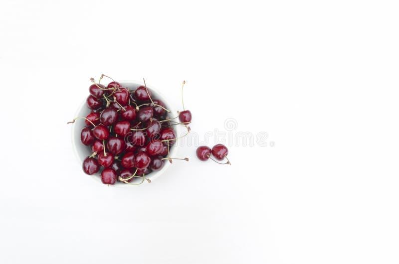 平的在一块玻璃板的位置新鲜的成熟甜樱桃 ?? 在碗的樱桃在白色背景 免版税库存照片