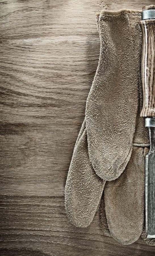 平的在木板的凿子防护手套 免版税图库摄影
