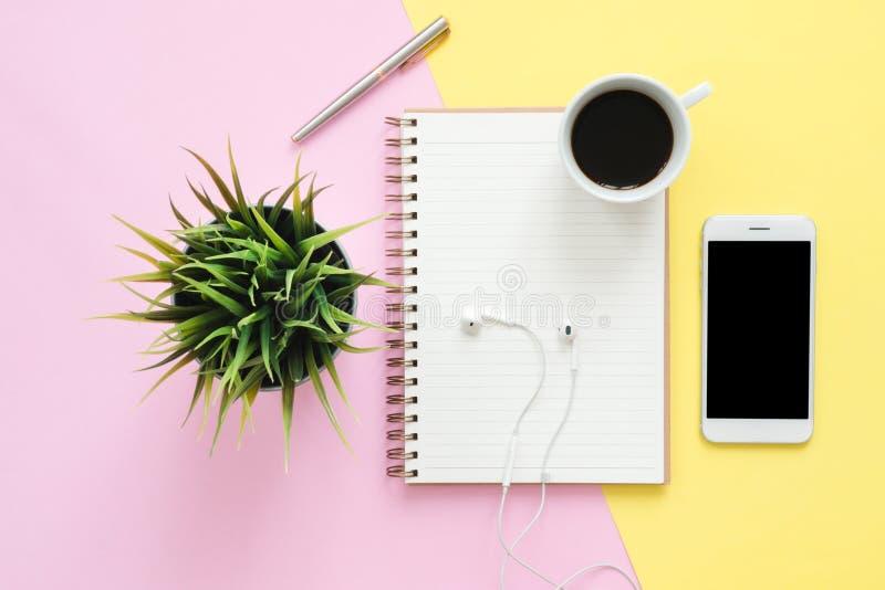 平的工作空间位置顶视图与白色空白的笔记本、耳机、咖啡杯和嘲笑的在淡色背景的电话 免版税库存图片
