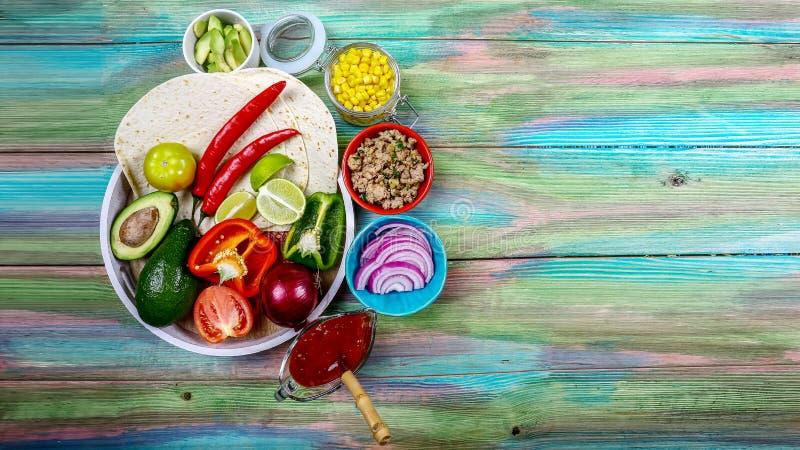 平的玉米粉薄烙饼和做在土气背景,顶视图,边界墨西哥烹调的炸玉米饼或面卷饼的各种各样的菜 图库摄影