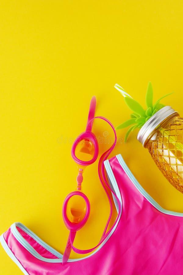 平的被放置的构成、夏天五颜六色的背景与桃红色泳装和海滩对象在黄色背景 复制文本的空间 免版税库存图片